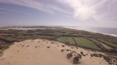 Aerial view over ocean grass sand dunes at sunny day - Torres Vedras, Portugal Stock Footage