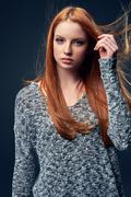 Beautiful red haired female in grey sweater - stock photo
