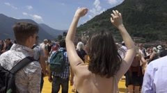 "Christo and Jeanne-Claude's ""Floating Piers"" - Girl Waving Hands in The Air Stock Footage"