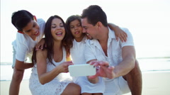 Smiling Latin American family making video diary on the beach Stock Footage