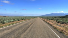 POV- Two lane road past sage juniper plain toward distant mountain Stock Footage