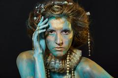 Model with gold and green body art. - stock photo