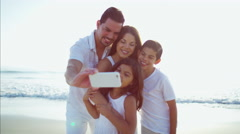 Latin American family making video diary on beach vacation Stock Footage
