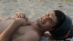 Handsome man with motorcycle helmet relaxing on the beach, close-up Stock Footage
