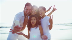 Laughing Spanish family having fun with taking a photo on the beach Stock Footage