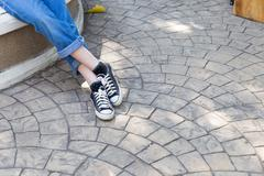 girl wearing jeans and sneaker sitting and waiting - stock photo