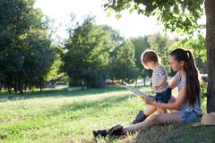 Young stylish mother and toddler reading book at garden during summer fun Stock Photos