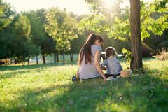 Mother and toddler sitting under the tree during summer leisure Stock Photos