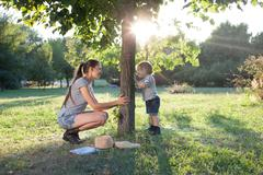 Mother and toddler playing the hide-and-seek outdoors Stock Photos