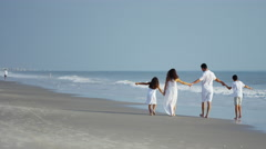Attractive Latin American family walking on the beach Stock Footage