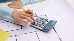 Woman with blueprint counting on calculator Stock Footage