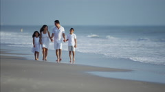 Happy Hispanic family walking on beach holiday Stock Footage