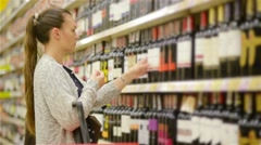 Woman shopping for wine or other alcohol in a bottle store standing in front of Stock Footage