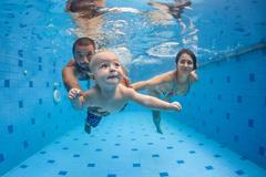 Happy full family swim and dive underwater in swimming pool Kuvituskuvat
