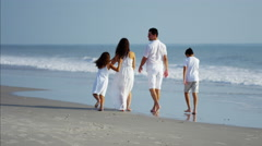 Carefree Spanish children relaxing with parents by ocean Stock Footage