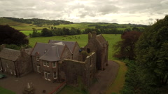 Aerial shot flying past country house and across british countryside Stock Footage