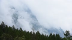 Clouds rolling in over mountain slope with pine trees in the Alps Stock Footage