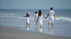 Young Spanish family walking together on the beach outdoors Stock Footage