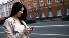 Charming young brunette woman is distracted with texting while standing by busy Stock Footage