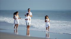 Latin American parents in white clothing enjoying time with children by ocean Stock Footage