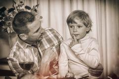Father with his son sitting on lap at home in the living room - stock photo