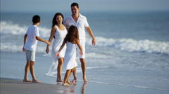 Young Spanish family in white clothing spending leisure time by ocean Stock Footage