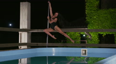 Graceful woman poledance artist performing fitness pole dance at night Stock Footage