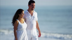 Beautiful Spanish couple in white clothing spending leisure time by ocean Stock Footage