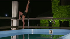 Slow motion of flexible woman performing fitness pole dance at night Stock Footage