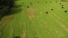 Aerial track acoss green field to reveal old churchyard - stock footage