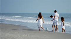 Happy Spanish children enjoying vacation with parents playing with ball on beach Stock Footage