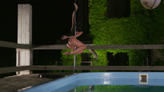 Fit girl poledancer performs fitness pole dance spins beside pool at night Stock Footage