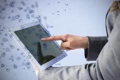 Businesswoman using a tablet pc against sphere of icons Stock Photos