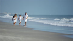 Latin American family playing together on beach vacation with ball Stock Footage