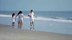 Happy Hispanic family having fun with ball on beach holiday Stock Footage