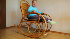 girl swinging on wicker rocking chair in room - stock footage