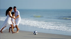 Latin American family playing together on beach holiday with soccer ball Stock Footage