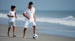 Young Spanish father and son having fun with football ball on beach holiday Stock Footage