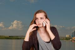 A beautiful woman chatting via phone and looking away against big blue sky and - stock photo