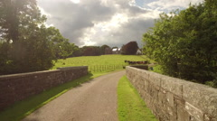 Aerial move across stone bridge and across country field - stock footage