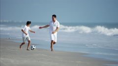 Latin American father and son playing soccer ball on beach vacation Stock Footage