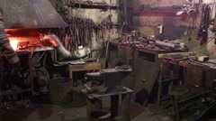 Blacksmith working on metal on anvil at forge. Arkistovideo