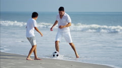 Carefree Hispanic father and son playing with soccer ball on beach holiday Stock Footage