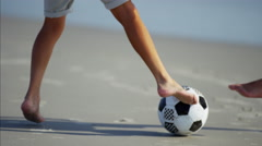 Feet of Hispanic father and son playing with soccer ball on the beach Stock Footage