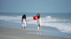Spanish mum and daughter playing together on beach vacation with red ball Stock Footage