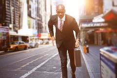 Businessman running against blurry new york street - stock photo