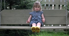 Little Cute Girl Swaying on Wooden Chain Swing Outdoor Stock Footage