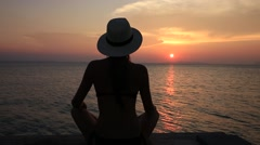 Girl in a straw hat sitting on the beach during sunset. Koh Samui, Thailand - stock footage
