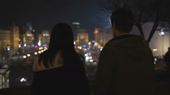 Couple of teenagers looking at night city lights, preparing to run away together - stock footage