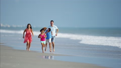 Latin American parents and children having fun on beach holiday Stock Footage